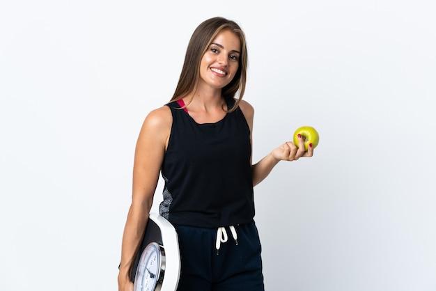 기계 무게와 사과와 흰 배경에 고립 된 젊은 우루과이 여자