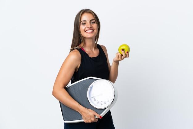 기계 무게와 사과와 흰 벽에 고립 된 젊은 우루과이 여자