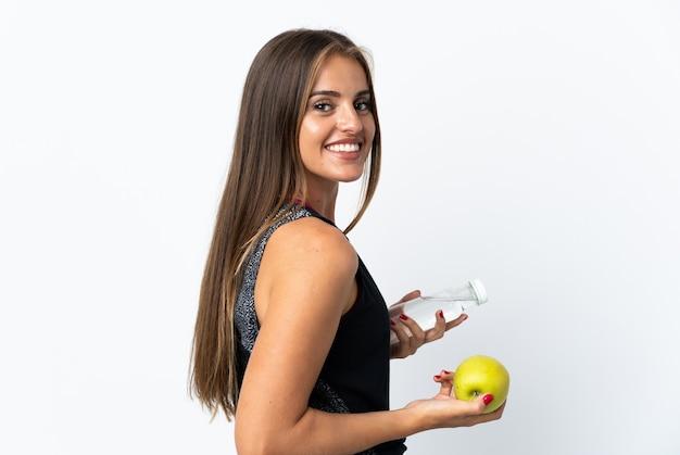 リンゴと水のボトルで白で隔離の若いウルグアイの女性