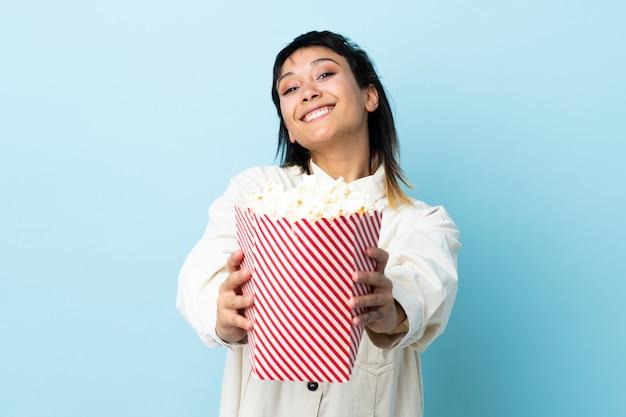 Молодая уругвайская женщина над изолированной синей стеной держит большое ведро попкорна