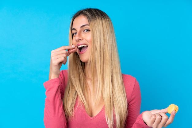 Молодая уругвайская женщина над изолированной синей стеной держит красочные французские макароны и ест это