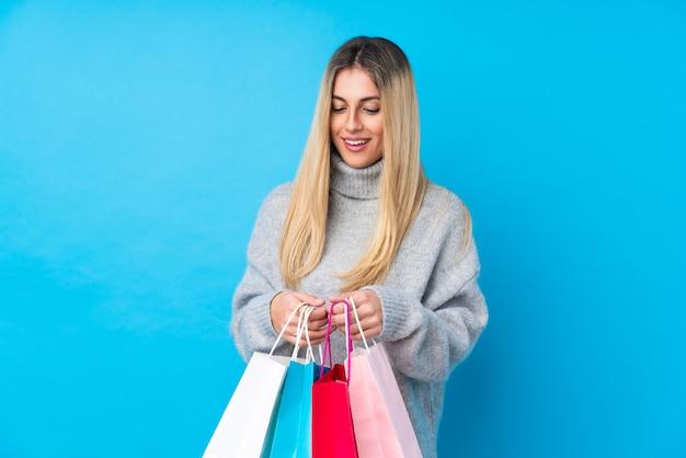 쇼핑백을 들고 내부를 찾고 격리 된 파란색 벽에 젊은 우루과이 여자