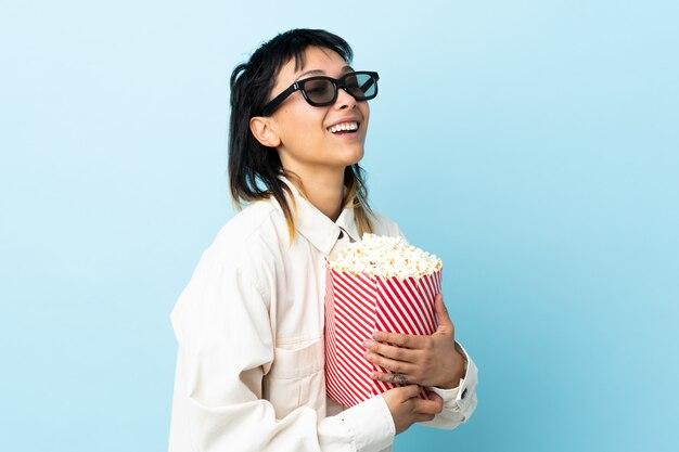 Молодая уругвайская женщина над изолированной синей стеной с 3d-очками и с большим ведром попкорна