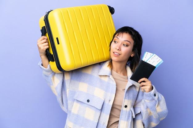 スーツケースとパスポートの休暇で孤立した紫色の背景に若いウルグアイの女性