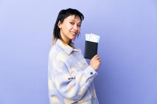 Молодая уругвайская женщина над фиолетовой стеной счастлива в отпуске с паспортом и билетами на самолет