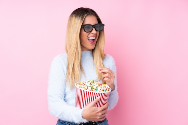 Young uruguayan woman with 3d glasses and holding a big bucket of popcorns while looking side