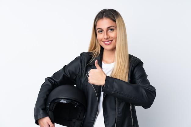 親指ジェスチャーを与える分離の白い壁の上のオートバイのヘルメットを持つ若いウルグアイ女性