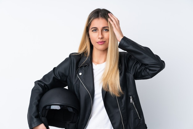 Young uruguayan woman with a motorcycle helmet over isolated white wall unhappy and frustrated with something. negative facial expression