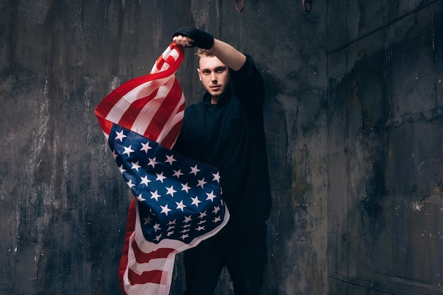 Молодой патриот сша с развевающимся американским флагом