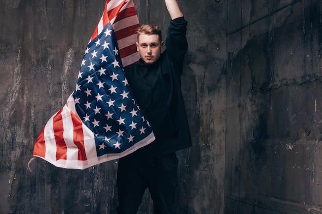 Молодой патриот сша с развевающимся национальным флагом