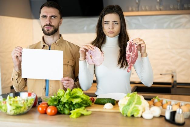 Молодая вегетарианская пара показывает, что не любит мясо и предпочитает свежие овощи