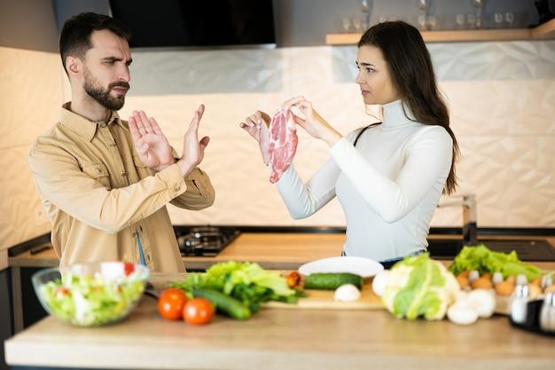 Молодой вегетарианец показывает, что нельзя есть мясо и предпочитать свежие овощи