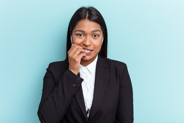 Young venezuelan business woman isolated on blue background biting fingernails, nervous and very anxious.