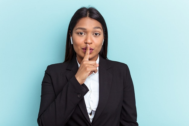 Young venezuelan business woman isolated on blue background keeping a secret or asking for silence.
