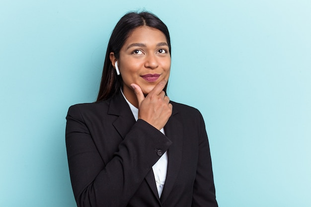 Young venezuelan business woman isolated on blue background looking sideways with doubtful and skeptical expression.