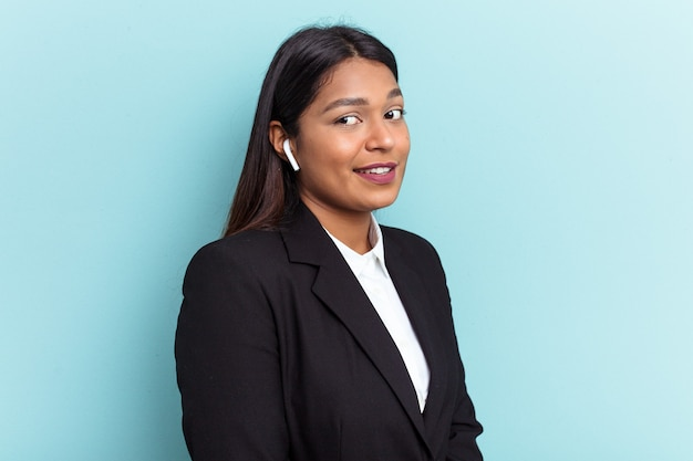 Young venezuelan business woman isolated on blue background looks aside smiling, cheerful and pleasant.