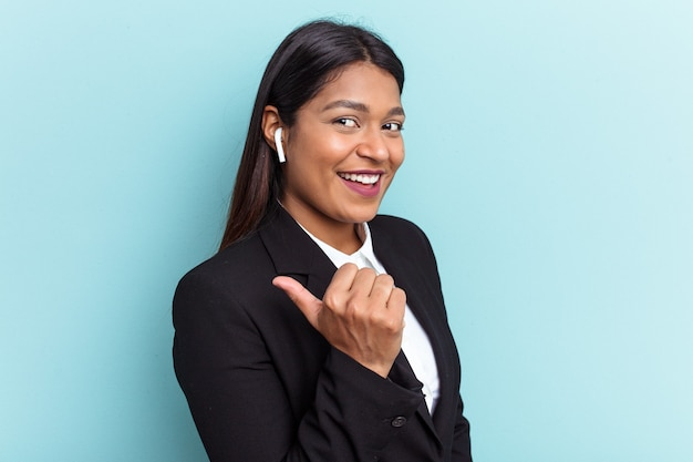 Young venezuelan business woman isolated on blue background points with thumb finger away, laughing and carefree.
