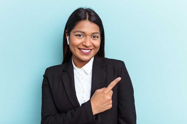Young venezuelan business woman isolated on blue background smiling and pointing aside, showing something at blank space.