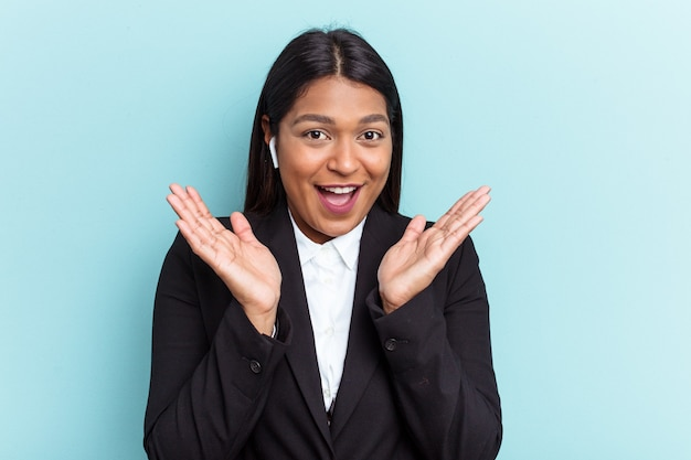 Young venezuelan business woman isolated on blue background surprised and shocked.