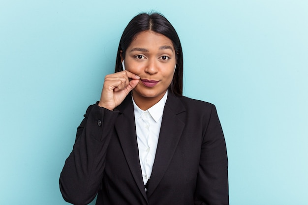 Young venezuelan business woman isolated on blue background with fingers on lips keeping a secret.