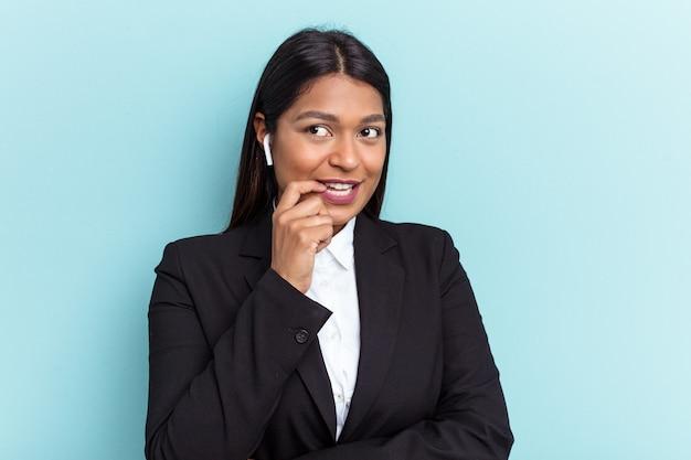 青い背景に孤立した若いベネズエラのビジネス女性は、コピースペースを見ている何かについて考えてリラックスしました。