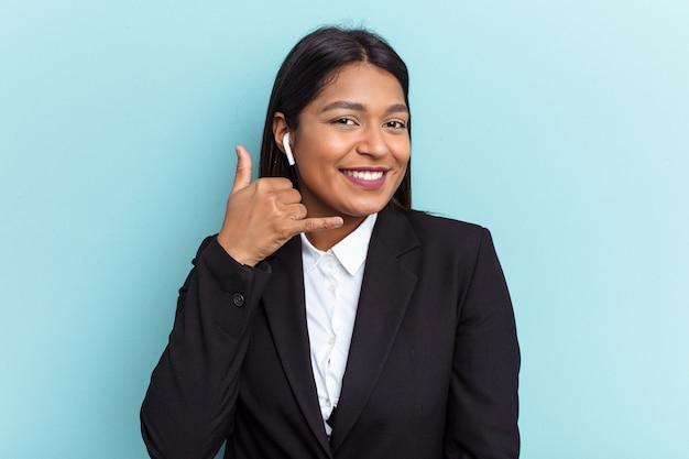 파란색 배경에 격리된 젊은 베네수엘라 비즈니스 여성은 손가락으로 휴대전화 통화 제스처를 보여줍니다.