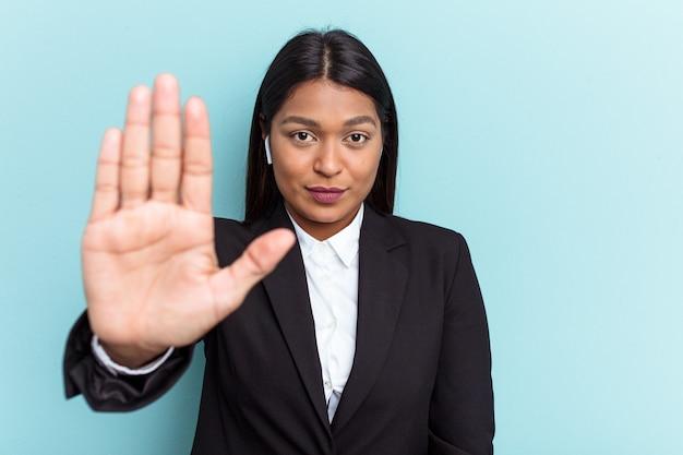 青の背景に孤立した若いベネズエラのビジネス女性は、一時停止の標識を示す伸ばした手で立って、あなたを防ぎます。
