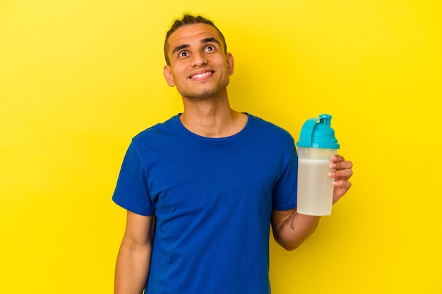 Young venezuelan man drinking a protein shake isolated on yellow background dreaming of achieving goals and purposes Premium Photo