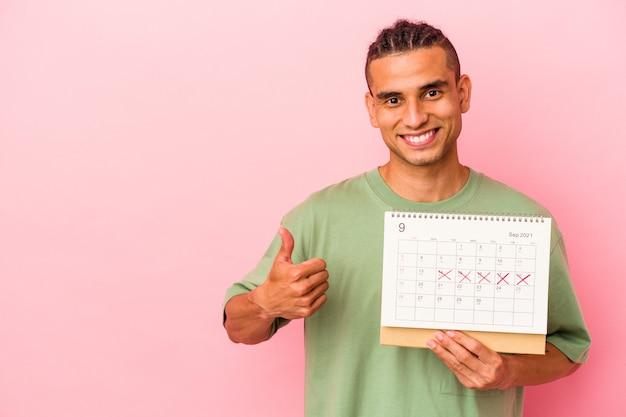 Молодой венесуэльский мужчина держит календарь на розовом фоне, улыбаясь и поднимая палец вверх