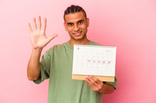 ピンクの背景に分離されたカレンダーを保持している若いベネズエラの男は、指で5番目を示す陽気な笑顔。