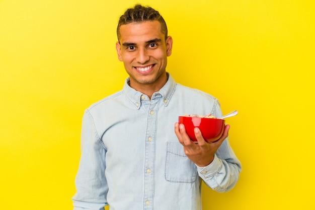 幸せ、笑顔、陽気な黄色の背景に分離されたシリアルボウルを保持している若いベネズエラの男。