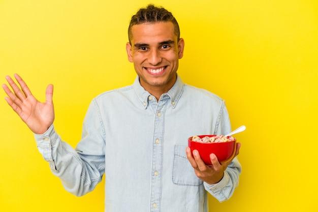 黄色の背景で隔離のシリアルボウルを保持している若いベネズエラの男
