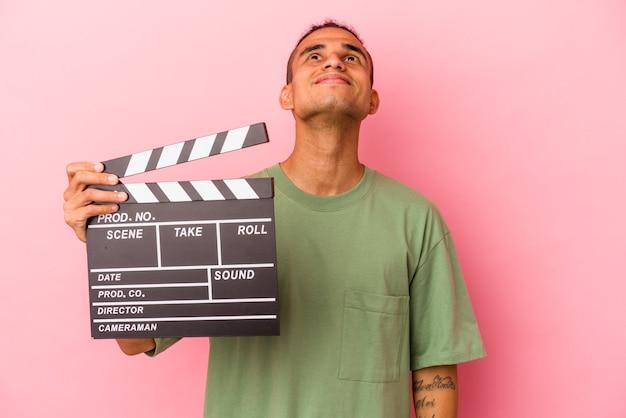 目標と目的を達成することを夢見てピンクの背景に分離されたカチンコを保持している若いベネズエラ人