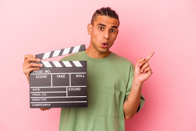 側面を指しているピンクの背景に分離されたカチンコを保持している若いベネズエラの男
