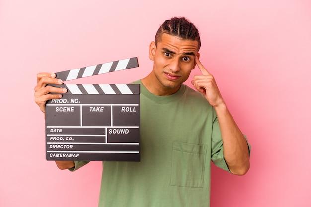 Молодой венесуэльский мужчина держит хлопушку, изолированную на розовом фоне, показывая жест разочарования указательным пальцем.