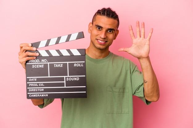 ピンクの背景に分離されたカチンコを持っている若いベネズエラ人は、指で5番を示して陽気に笑っています。