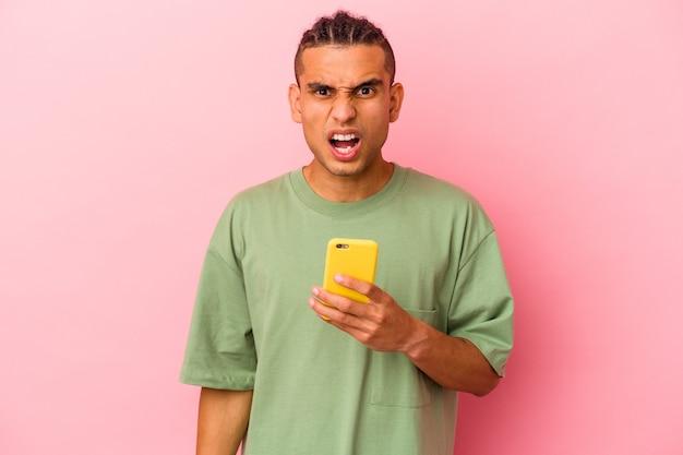 Молодой венесуэльский мужчина, держащий мобильный телефон, изолированный на розовом фоне, кричит очень сердито и агрессивно.