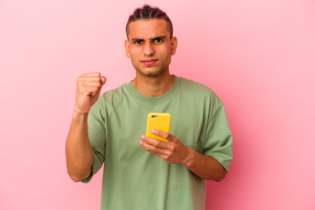 Молодой венесуэльский мужчина, держащий мобильный телефон, изолированный на розовом фоне, показывает кулак на камеру, агрессивное выражение лица.