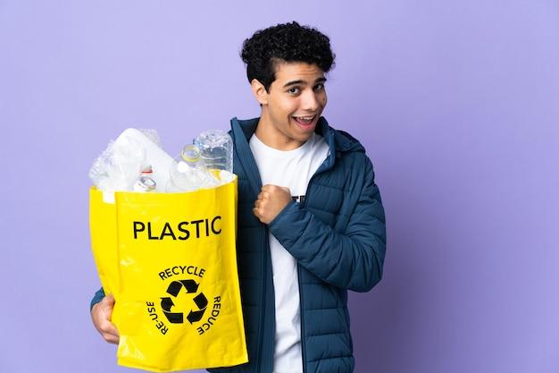 Young venezuelan man holding a bag full of plastic bottles celebrating a victory