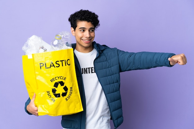 Young venezuelan man holding a bag full of plastic bottles giving a thumbs up gesture