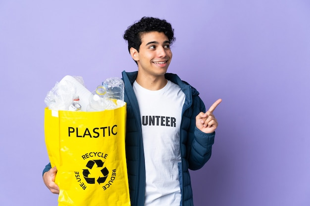 Young venezuelan man holding a bag full of plastic bottles pointing up a great idea