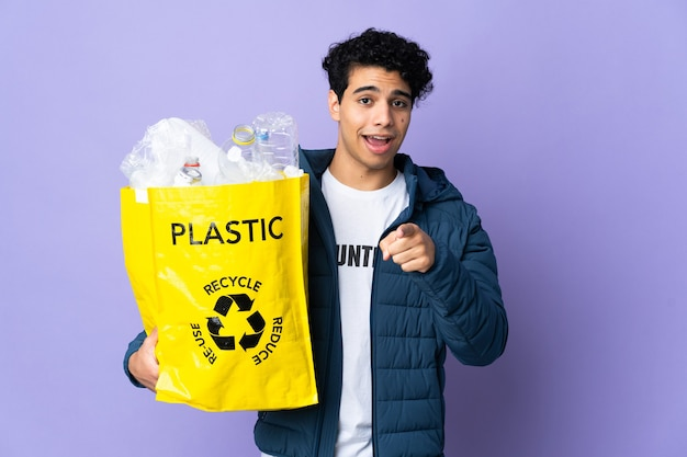 Young venezuelan man holding a bag full of plastic bottles surprised and pointing front