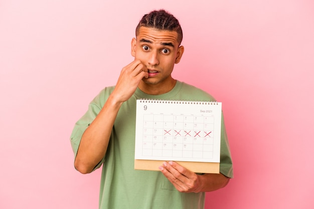 Young venezuelan man holding a calendar isolated on pink background biting fingernails, nervous and very anxious.