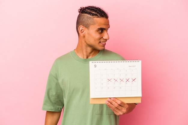 Young venezuelan man holding a calendar isolated on pink background looks aside smiling, cheerful and pleasant.