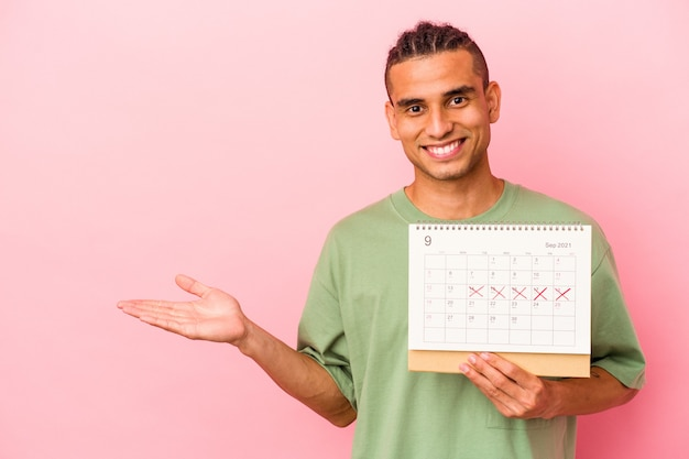 Young venezuelan man holding a calendar isolated on pink background showing a copy space on a palm and holding another hand on waist.