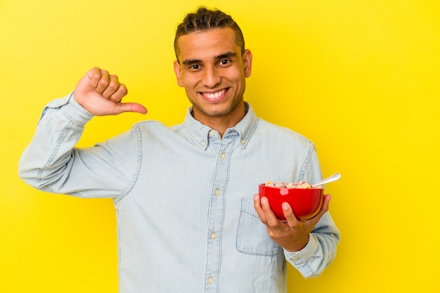 Young venezuelan man holding a cereals bowl isolated on yellow background feels proud