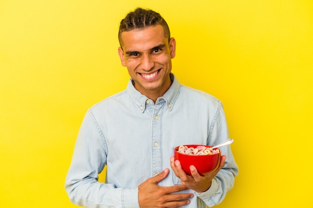 Young venezuelan man holding a cereals bowl isolated on yellow background laughing and having fun