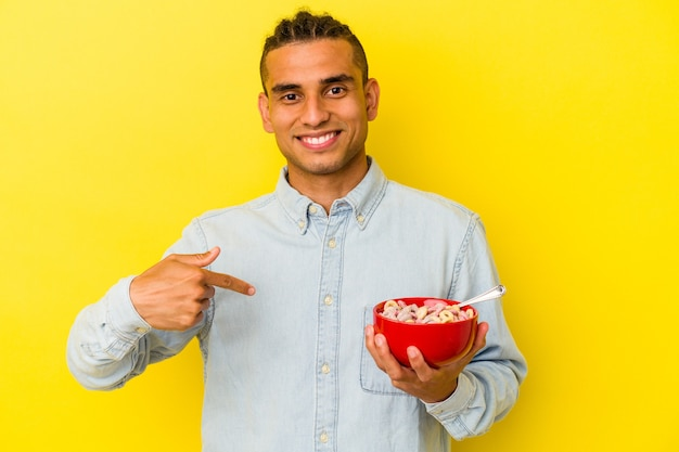 Young venezuelan man holding a cereals bowl isolated on yellow background person pointing by hand to a shirt copy space, proud and confident