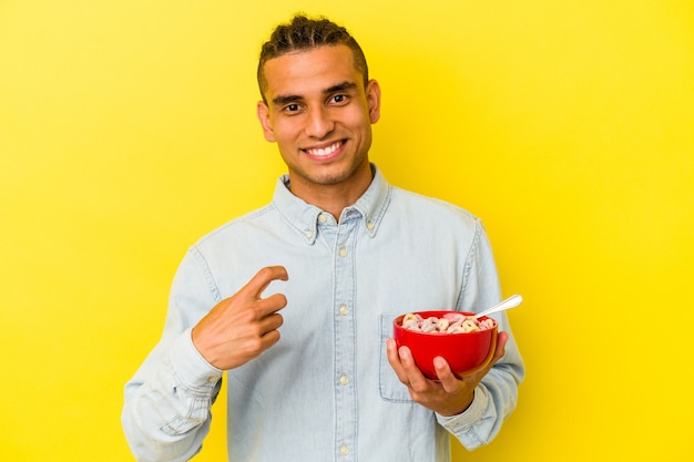 Young venezuelan man holding a cereals bowl isolated on yellow background pointing with finger