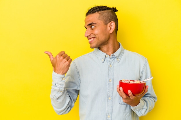 Young venezuelan man holding a cereals bowl isolated on yellow background points with thumb